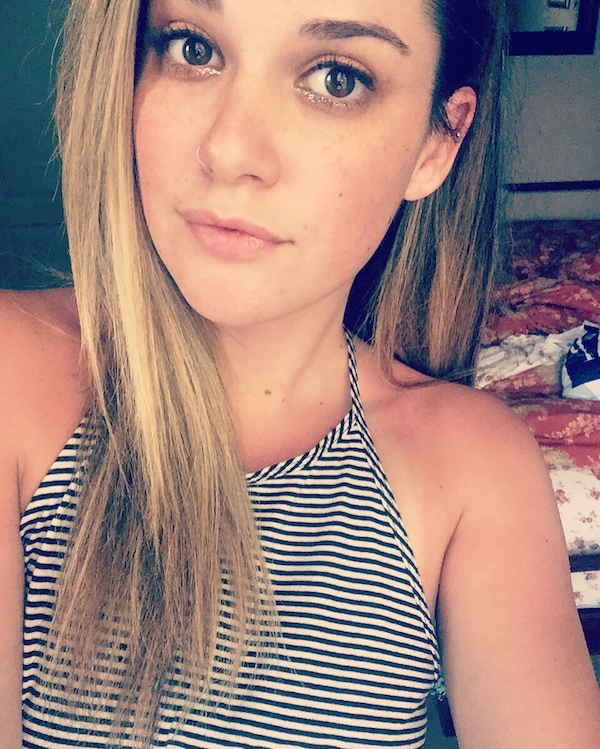 Girl with big eyes wearing a sleeveless top clicks a selfie