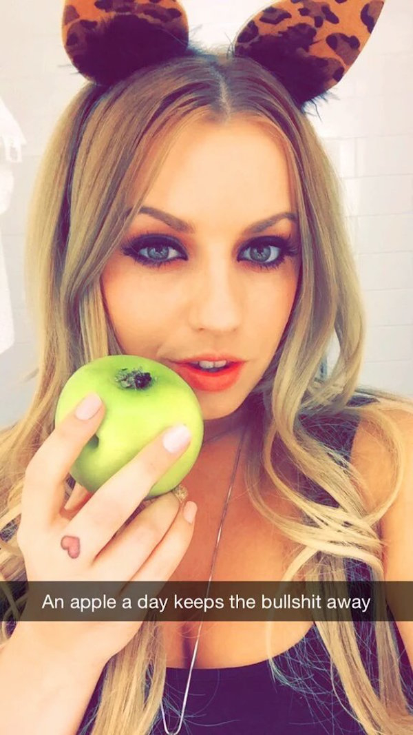 Cute blonde with beautiful light eyes and red juicy lips poses in cat ears and juicy cleavage showing black top