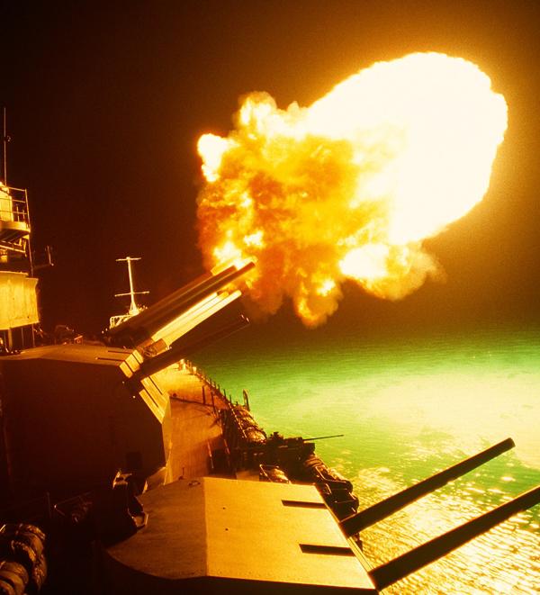 USS Missouri Battleship firing guns in the night.