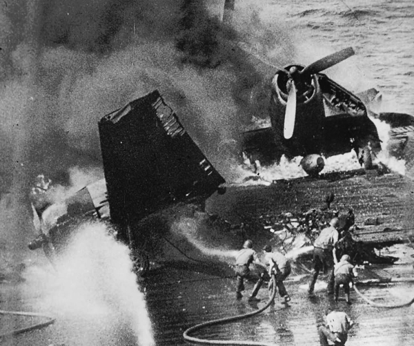 Soldiers on board spraying water jets to control the flames arising from the plane crash on USS Missouri