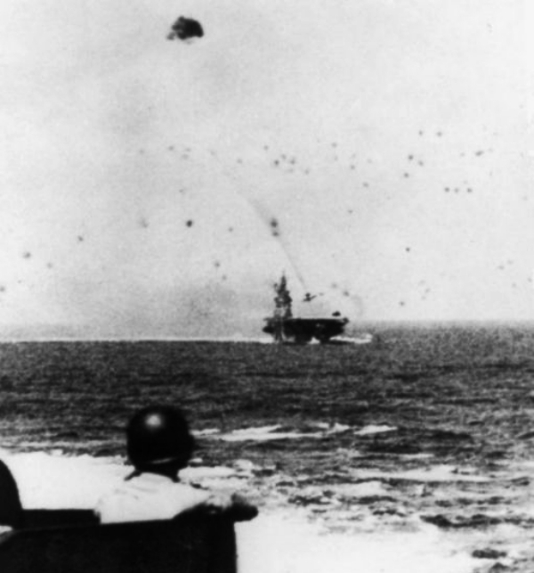 A black and white photograph taken from a battleship of a fighter plane crashing on the deck of USS Missouri