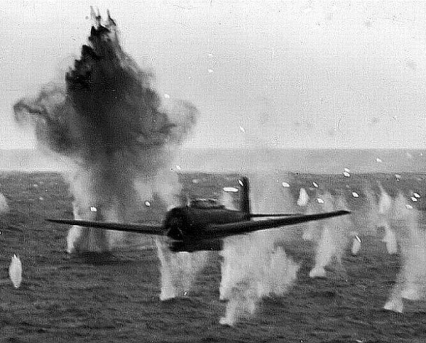 A black and white photograph of a fighter plane flying over sea, evading machine gun fire and projectiles that's causing parallel splashes in the water