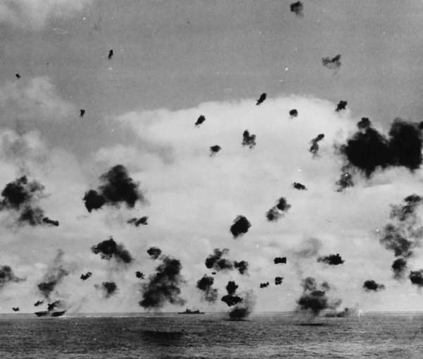 Many thick clumps of black smoke in the sky over a battleship caused due to rapid projectile firing on aircrafts.