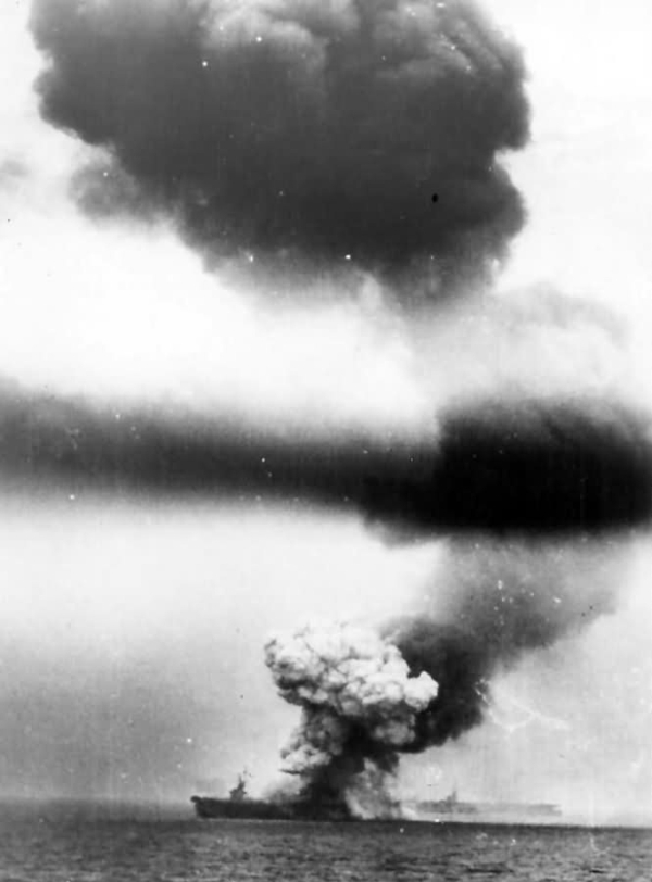 Clumps of black and white smoke rising from the deck of a battleship after an aircraft attack