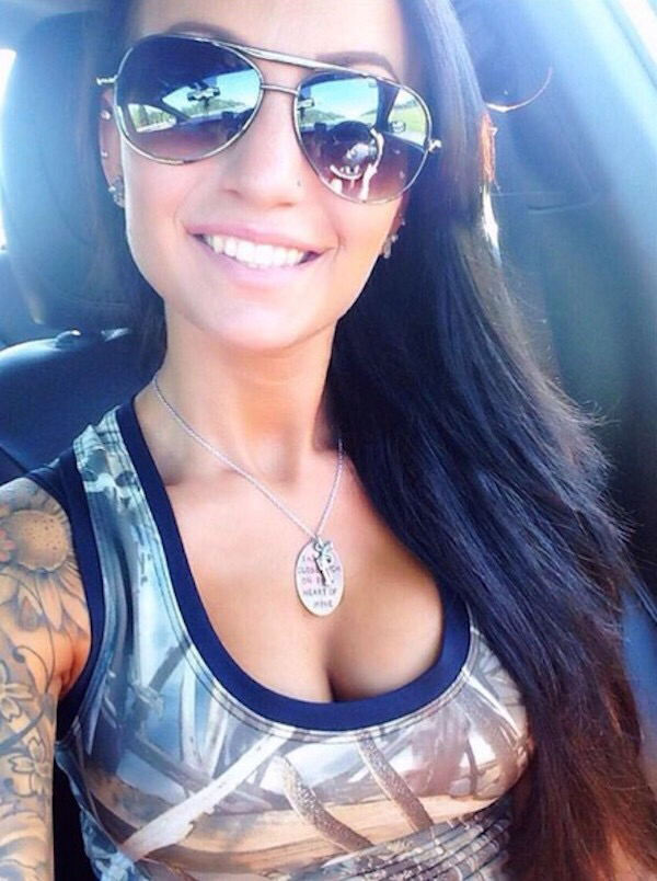 Punk chick with lot of tattoos and sunglasses clicking selfie in the car