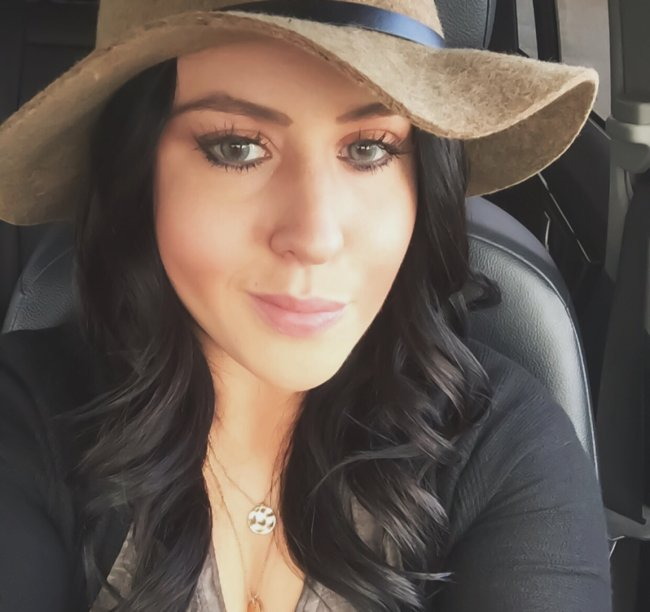 Gorgeous brunette with beautiful light eyes and full juicy lips takes selfie in beige hat, grey top, and black jacket
