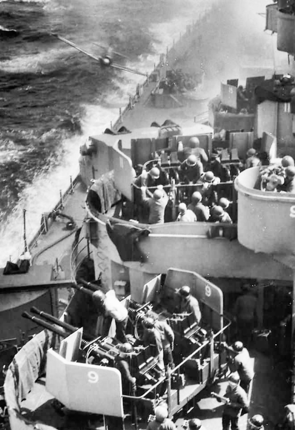 Soldiers rushing to take cover in the bunkers as a fighter plane approaches the deck of a battleship