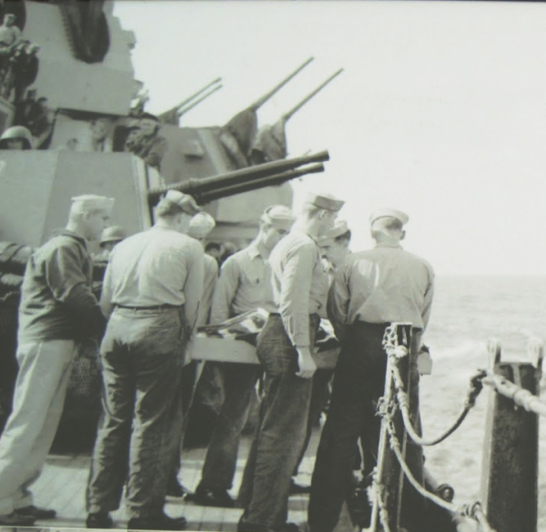 Sailors onboard USS Missouri carrying the dead body of the Japanese pilot for burial.