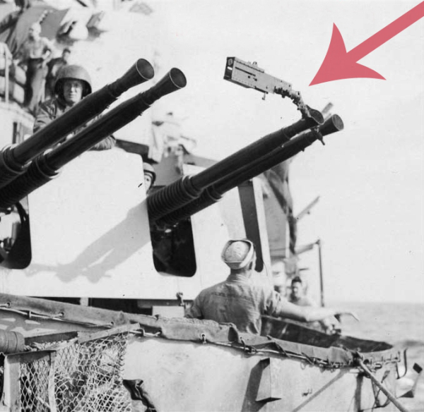 Black and White photograph of USS MIssouri with few soldiers and sailors. The red arrow is pointing at the muzzle brake attached to one of the AA guns.