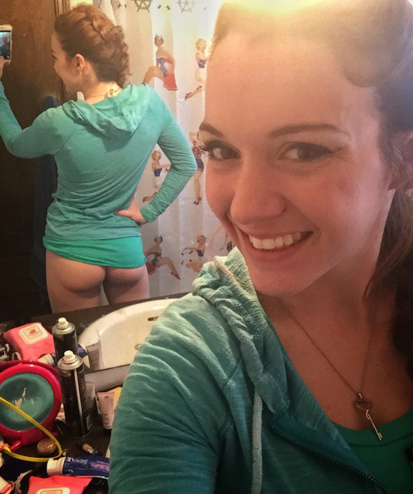 Brunette in green tee and hoodie smiles and takes selfie of cute supple naked butt cheeks