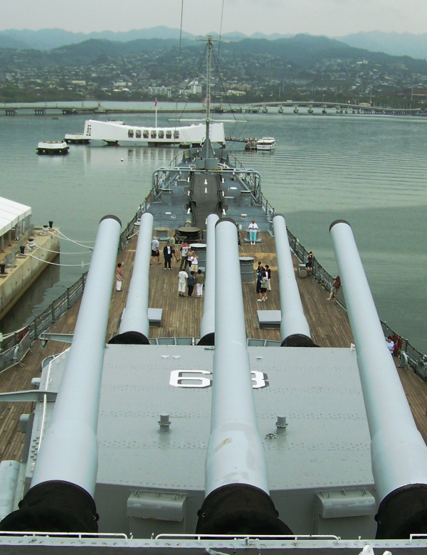 Modern day photograph of people walking onboard the reconstructed USS Missouri, exploring the memorials.