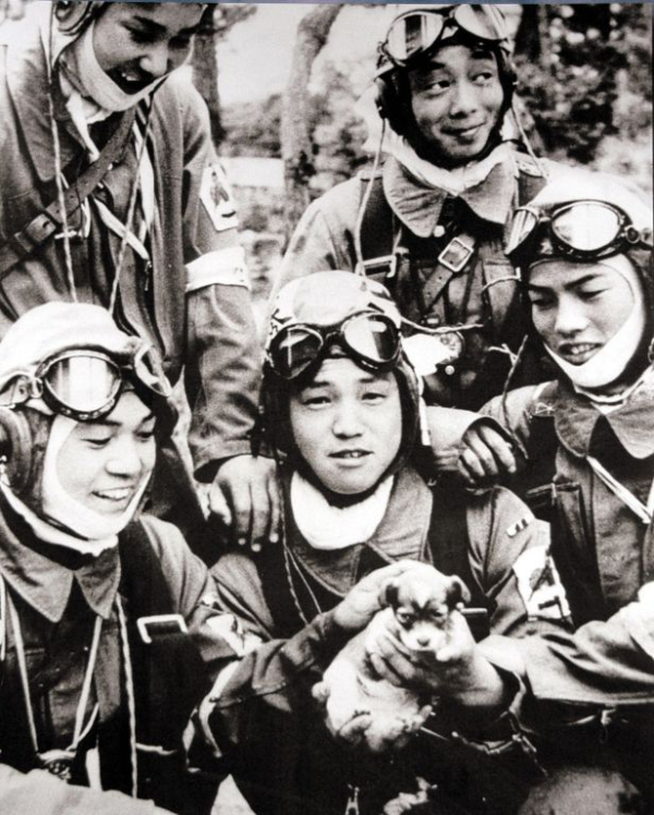 An old group photo of few pilots with a puppy.
