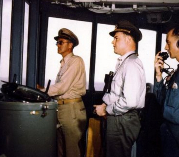 An old photograph of a commander, captain and operator onboard a battleship.
