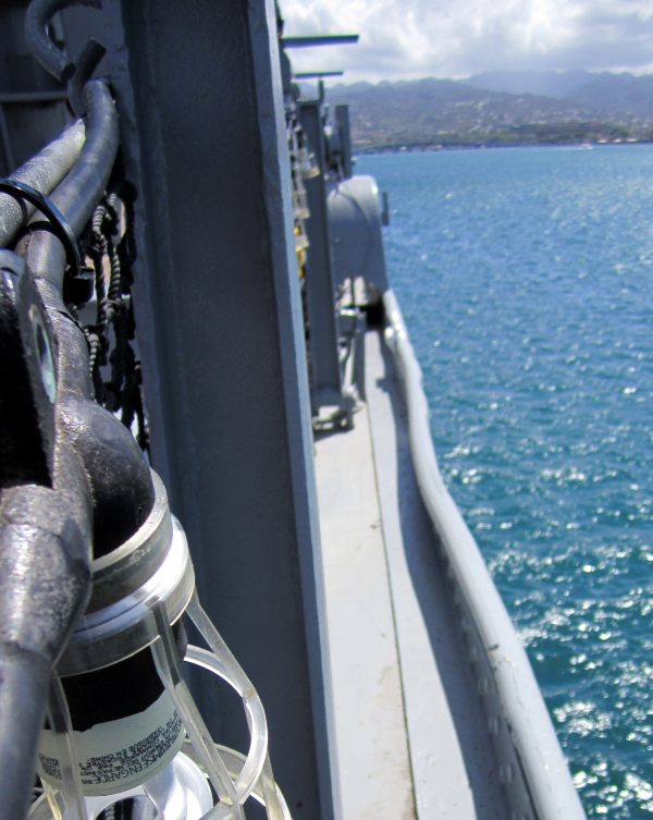 Picture taken from the deck of a ship that's near a small town on the sea coast on a bright warm day.