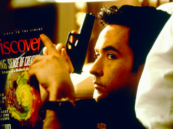 John Cusack in a black tee holds a gun while reading Discover magazine!