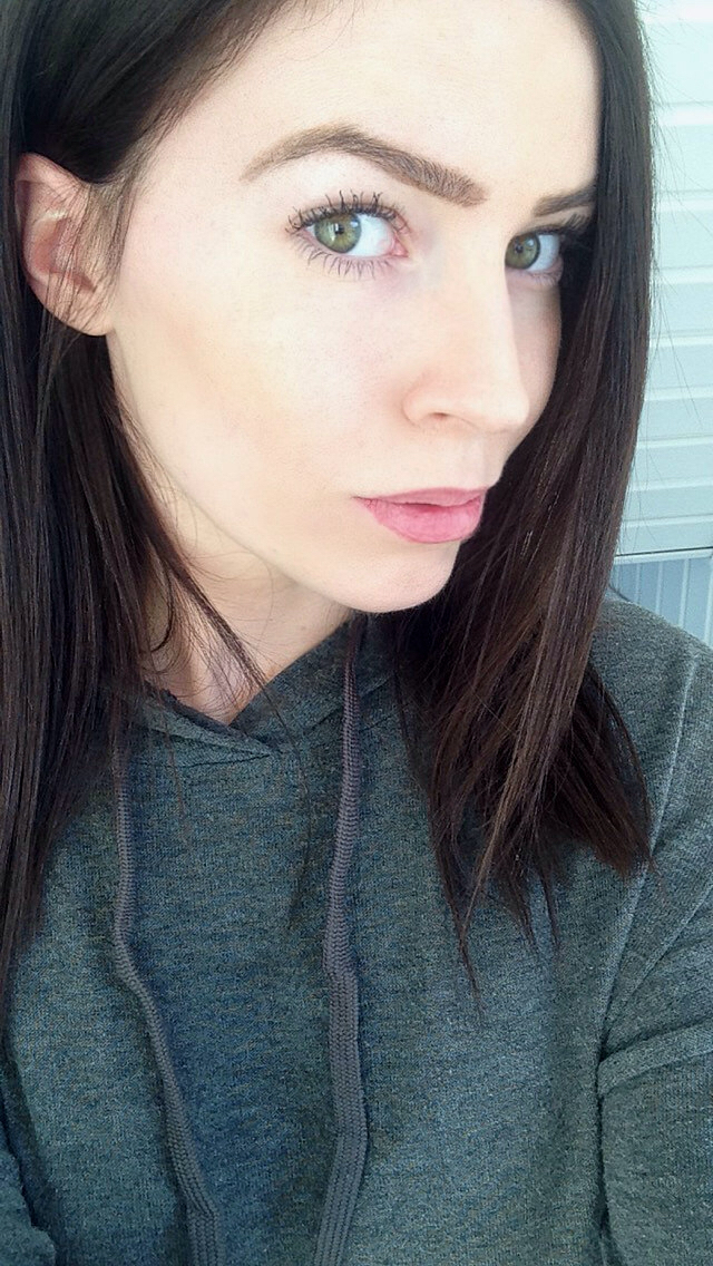 Gorgeous brunette with cat eyes and juicy pink lips takes selfie in grey top