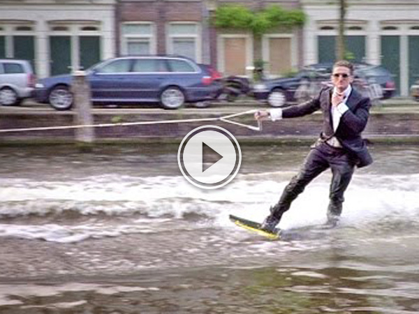 Picture of video of blonde guy in Amsterdam sporting shades and a black suit wake boarding.