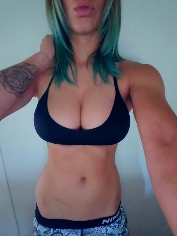 Sexy blonde with large size boobs, green short hair and floral wrist tattoo