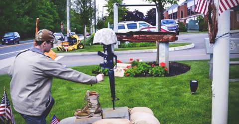Young guy paying his tribute to the memorial of a late US army veteran, Justin Fitch.