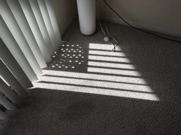 A shadow of the American flag falls on the floor because of the setting of the blinds