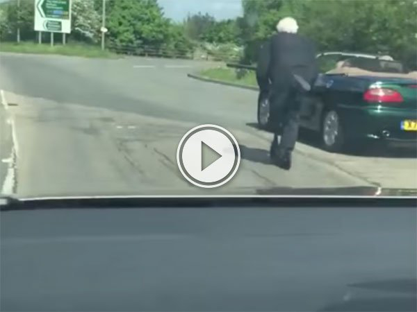 An old Man scooters down a busy road (Video)