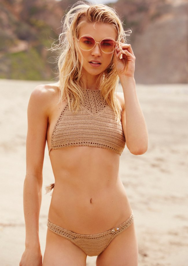 Hot blonde in nude tinted sunglasses and crochet bikini by the sea