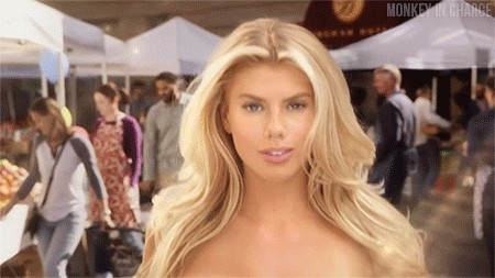 Hot blonde model adjusts her hair as she walks on the street while her boobs are bouncing heavily (GIF)
