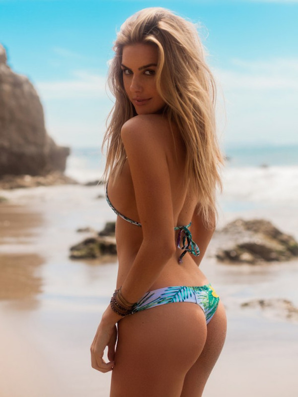 Hot blonde in sexy bikini looking back at the lens on the beach