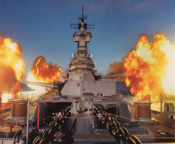 The guns of a battleship boom and create clouds of fire and smoke!