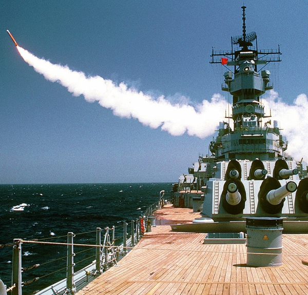 A surface to air missile leaves a trail of smoke as it is launched from a battleship!
