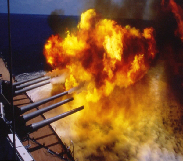 A Cloud of smoke and fire created by the booming guns of a warship!