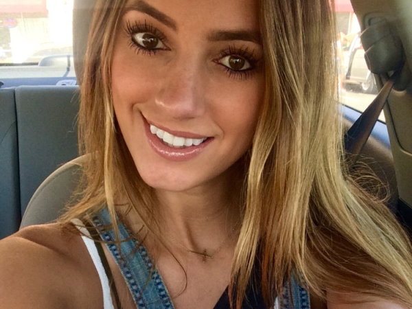 Cute blonde with beautiful brown eyes takes a selfie in a car.