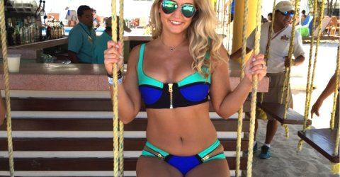 Voluptuous blonde with sexy thighs and perky boobs poses on swing in blue/black bikini