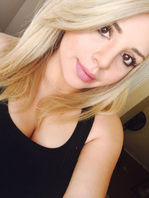 Beautiful blonde with juicy lips and brown eyes takes selfie in cleavage showing black top