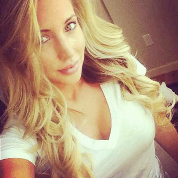 HOt blonde with blue eyes taking selfie in a white top