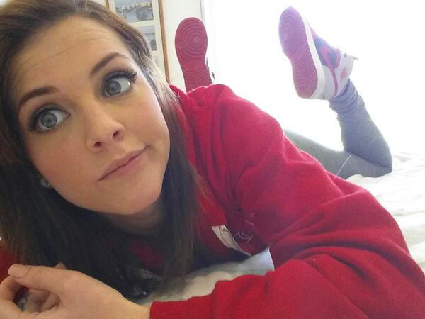 Girl with pretty big eyes making a face in the selfie in red sweatshirt and sneakers