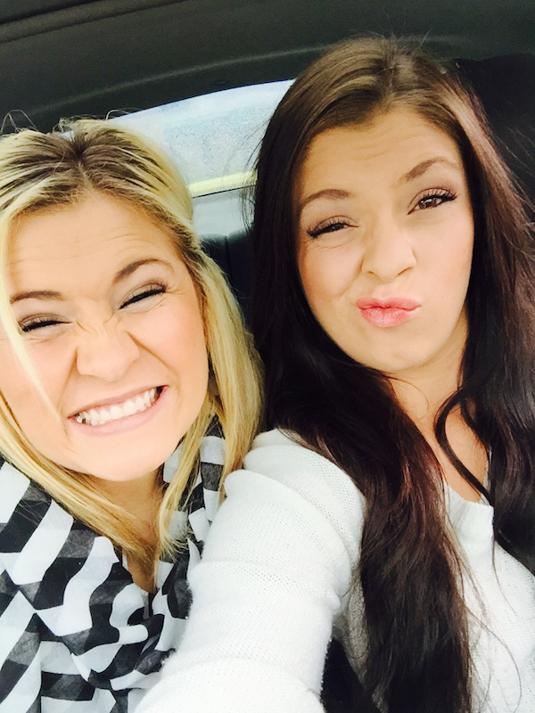 Girls in black and white tops fool around and pose for selfie