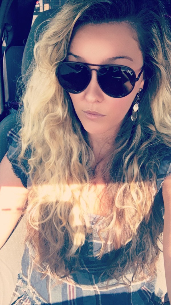 Beautiful mature woman clicking selfie with classic black full frame sunglasses, curly blonde cor hair and silver ong earrings