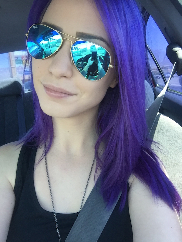 Pretty woman taking a car selfie with designer golden full frame, blue aviator sunglasses and blue hair