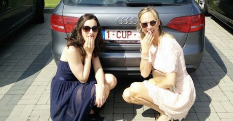 girl on left wearing backless halter neck deep blue knee length frock with cool glares and girl on right wearing white lace half sleeves tunic with stylish golden frame sunglasses while sitting togther in the back of Audi car with number plate - 1-CUP