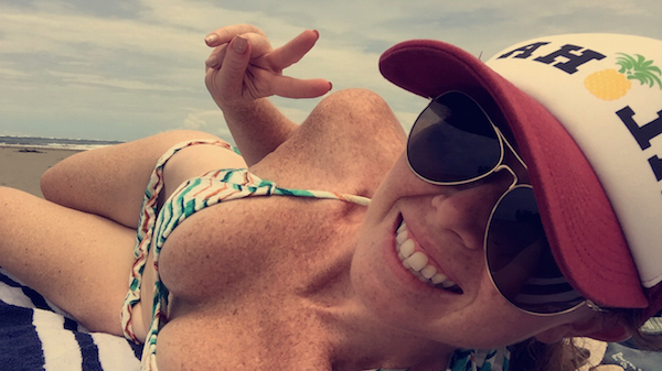 Cute bikini babe posing for a cheerful selfie in two piece, zig-zag pattren print bikini, full golden frame, brown, retro look sunglasses, white red cap with pineapple logo
