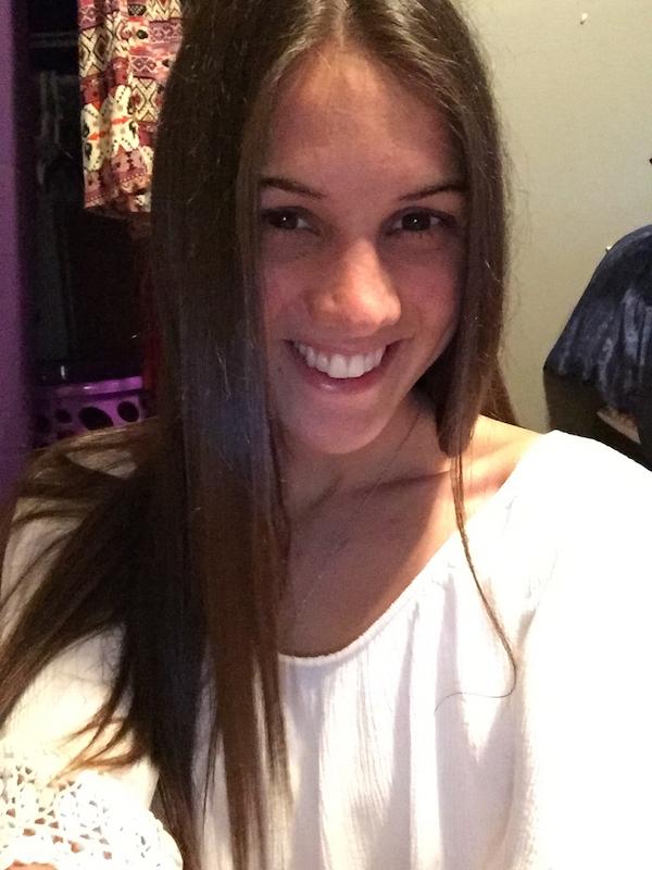 Blonde smiles for selfie in white top