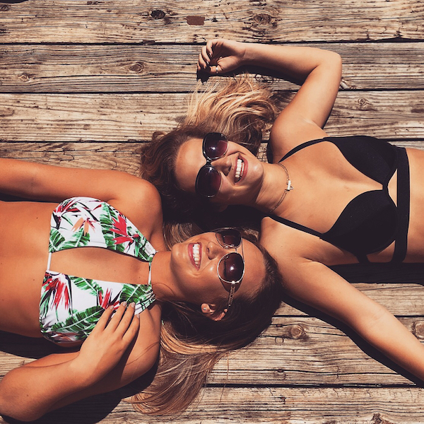 Happy friends lying reverse to each other to show thier sexy boobs in sexy bikini tops, tanned body and cool sunglasses