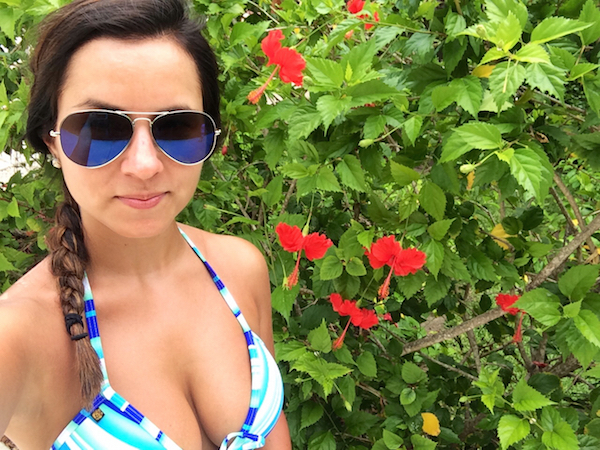Cute young girl looking gorgeous in white-blue triangle shaoe bikini top, cool navy blue aviator sunglasses and one side swept braid and showing off her sexy boobs with red hibiscus flowers in background