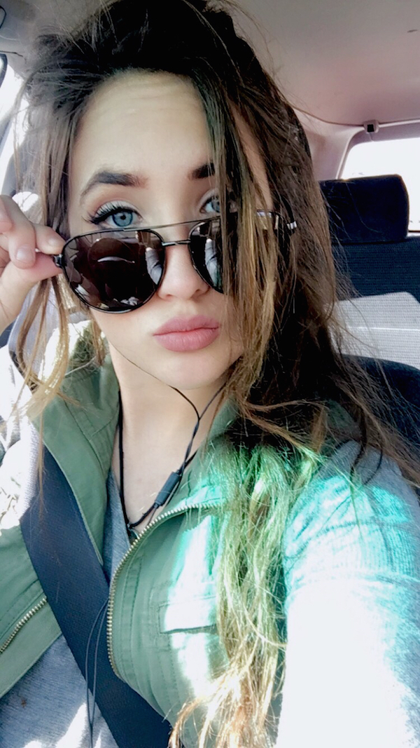 Very pretty and cute girl removing her sunglasses to show her sexy blue eyes with curved eyelashes and big pouty lips to click a selfie