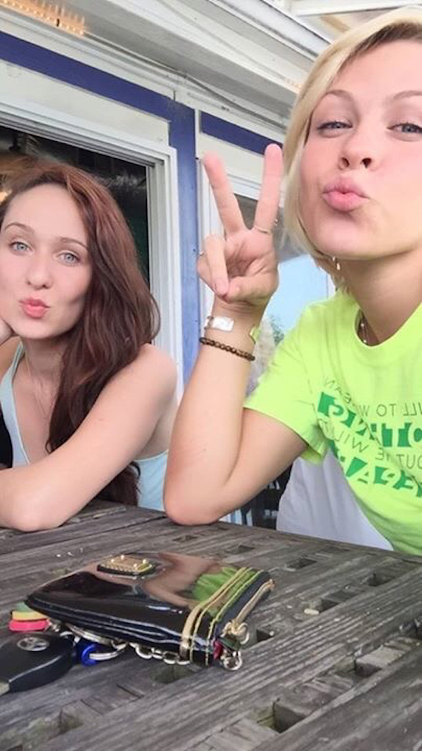 Slender girls in green and grey tops blow kisses at the camera