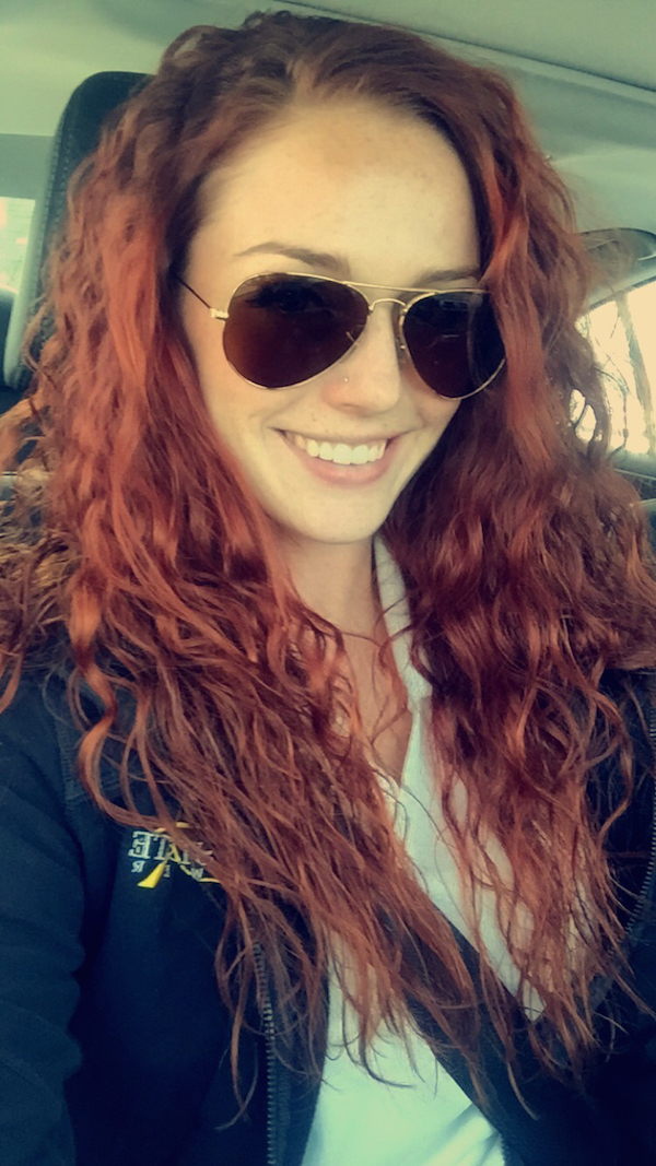 Hot girl clicking a car selfie to show her sexy gold frame, brown, aviator sunglasses with pretty smile and red curly hair