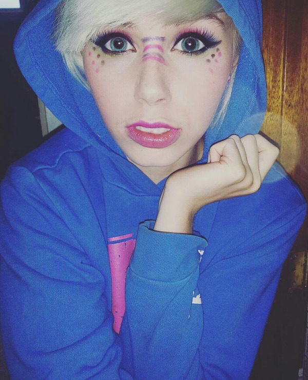 Ash blonde with blue eyes and facial makeup poses in blue hoodie