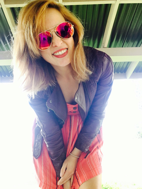 Gorgeous girl showing off her golden full frame, pink reflector sunglasses with short blonde color hair, sweet smile with beautiful teeth, stylish brown lleather jacket over red knee length frock