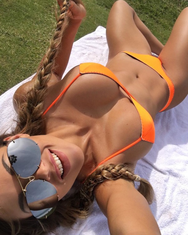 Sexy blonde taking a upside down slefie to show her big tight boobs in orange yellow two piece swimsuit, two beautiful braids and cool black aviator sunglasses